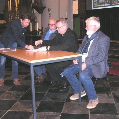 Het contract wordt door H. Scheijven ter ondertekening voorgelegd aan (van L naar R)   P. Slegers (secretaris), R. Schuffelers (pastoor/voorzitter) en H. van van Rossum (orgelbouwer)
